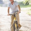Man outdoors on bike smiling — Stock Photo