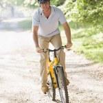 Man outdoors riding bike smiling — Stock Photo #4770188