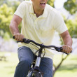 Man outdoors riding bike smiling — Stock Photo