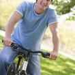 Man outdoors on bike smiling — Stock Photo #4770204