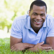 Man lying outdoors smiling - Stock Photo