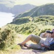 Royalty-Free Stock Photo: Man relaxing on cliffside path using binoculars