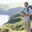Stock Photo: Mstanding on cliffside path holding map