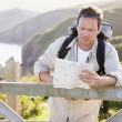 Man relaxing on cliffside path holding map - ストック写真