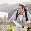 Man relaxing on cliffside path holding map and laughing - Stock Photo