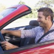 Man driving convertible car smiling - Stock Photo