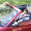 Man driving convertible car using cellular phone and smiling - Stock Photo