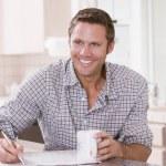 człowiek w kuchni czytanie gazety i uśmiechając się — Zdjęcie stockowe