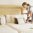 Maid making bed in hotel room smiling — Stock Photo