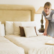Maid making bed in hotel room — Stock Photo #4770301