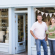 Couple standing in front of organic food store smiling — ストック写真