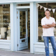 Man standing in front of organic food store smiling - Stock Photo