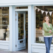 Woman standing in front of organic food store smiling - Stock Photo
