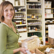 Woman in market looking at bread smiling — Stock Photo