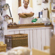 Man in birdhouse store smiling - Stock Photo