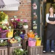 Woman working at flower shop smiling - Photo
