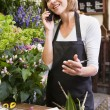 Woman working at flower shop using telephone and smiling — Stock Photo