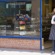 Woman standing in doorway of restaurant smiling — ストック写真