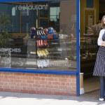 femme debout dans la porte du restaurant souriant — Photo