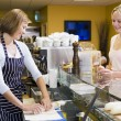 Woman standing at counter in restaurant serving customer smiling — Stockfoto #4770347