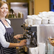 Woman making coffee in restaurant smiling — 图库照片