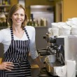Woman making coffee in restaurant smiling - Stok fotoğraf