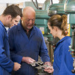 Three machinists in workspace by machine talking — Stock Photo