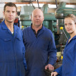 Three machinists in workspace by machine talking — Stock Photo #4770421