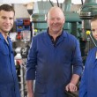 Three machinists in workspace by machine talking - Stock Photo