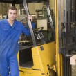 Photo: Warehouse worker standing by forklift