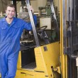 Warehouse worker standing by forklift — Stock Photo #4770429