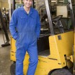 Warehouse worker standing by forklift — Stock Photo #4770430