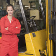 Stock Photo: Warehouse worker standing by forklift