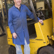 Warehouse worker standing by forklift — Stock Photo #4770438