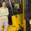 Warehouse worker standing by forklift — Stock Photo