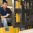 Warehouse worker in forklift — Stock Photo