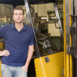 Warehouse worker standing by forklift — Stock Photo #4770450