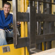 Stockfoto: Warehouse worker in forklift