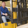 Warehouse worker in forklift — Stok fotoğraf