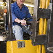Stock Photo: Warehouse worker in forklift