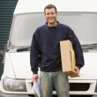 Deliveryperson standing with van holding clipboard and box smili — Stock Photo #4770469