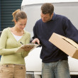 Two deliverypeople standing with van holding clipboard and box - Stock Photo