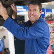 Stock Photo: Mechanic working under car smiling