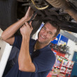 Mechanic working under car smiling — Stock Photo