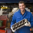 Mechanic holding car part smiling - Stock Photo