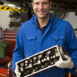 Mechanic holding car part smiling — Stock Photo