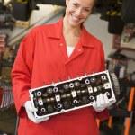 Mechanic holding car part smiling — Stock Photo #4770521