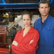 Two mechanics standing in garage - Stock Photo