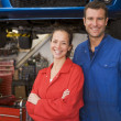 Two mechanics standing in garage smiling - Stockfoto