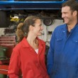 Stock Photo: Two mechanics standing in garage smiling